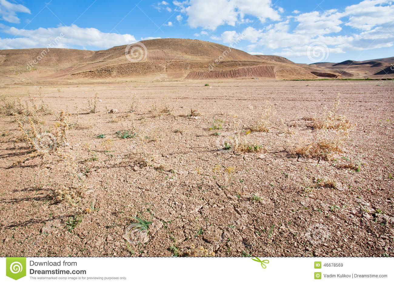 Mountains in the distance of the desert valley with dry soil under the scorching sun
