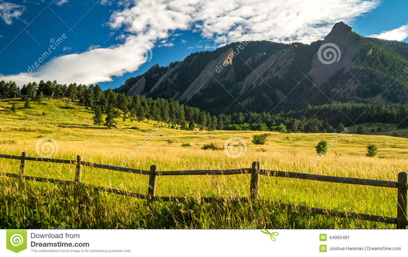 Mountains with grassy fields and a fence