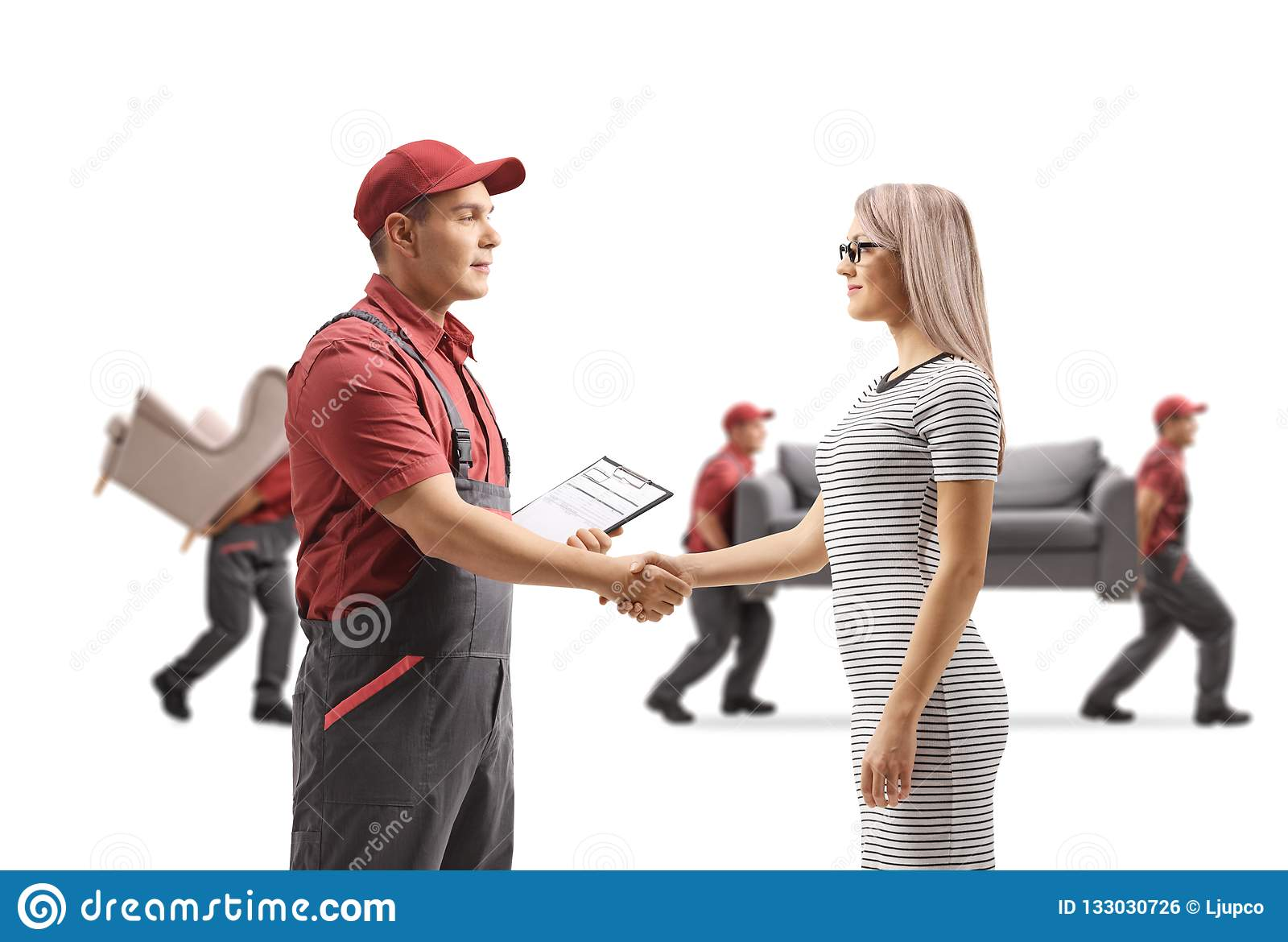 Mover shaking hands with a woman and movers carrying furniture i