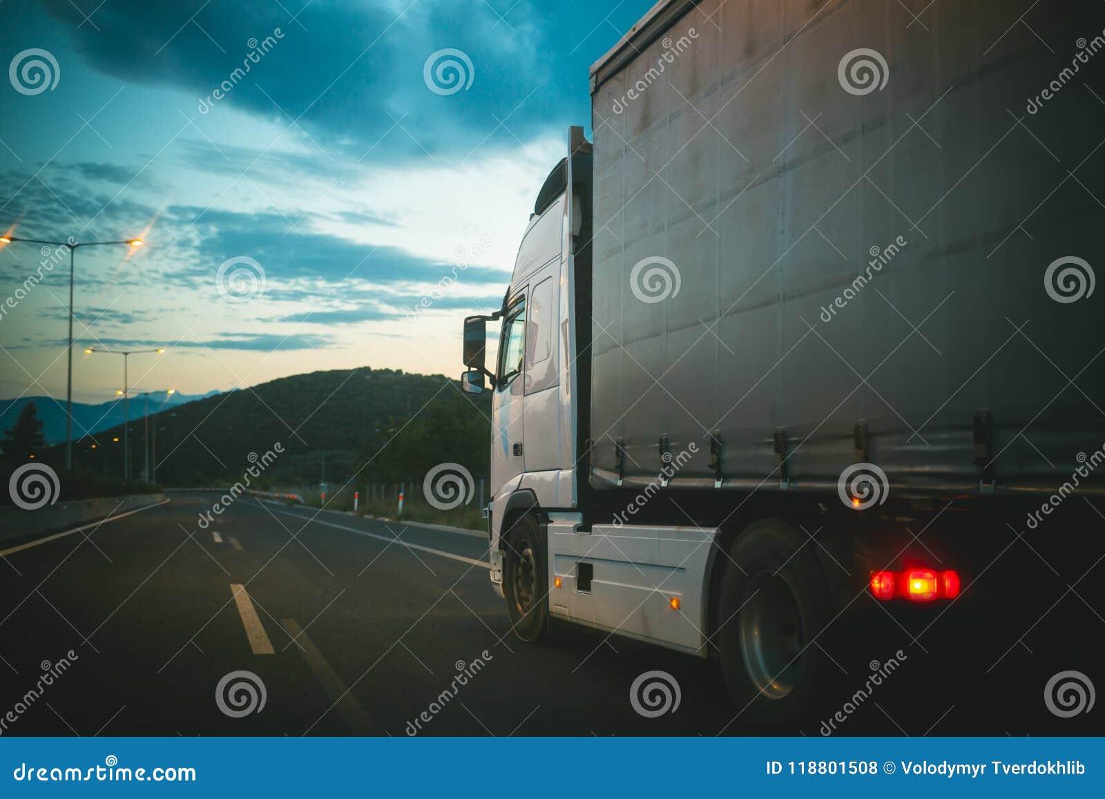 Movimentação do carro do caminhão na estrada na noite Carga do transporte do caminhão Transporte e expedição Velocidade e conceit