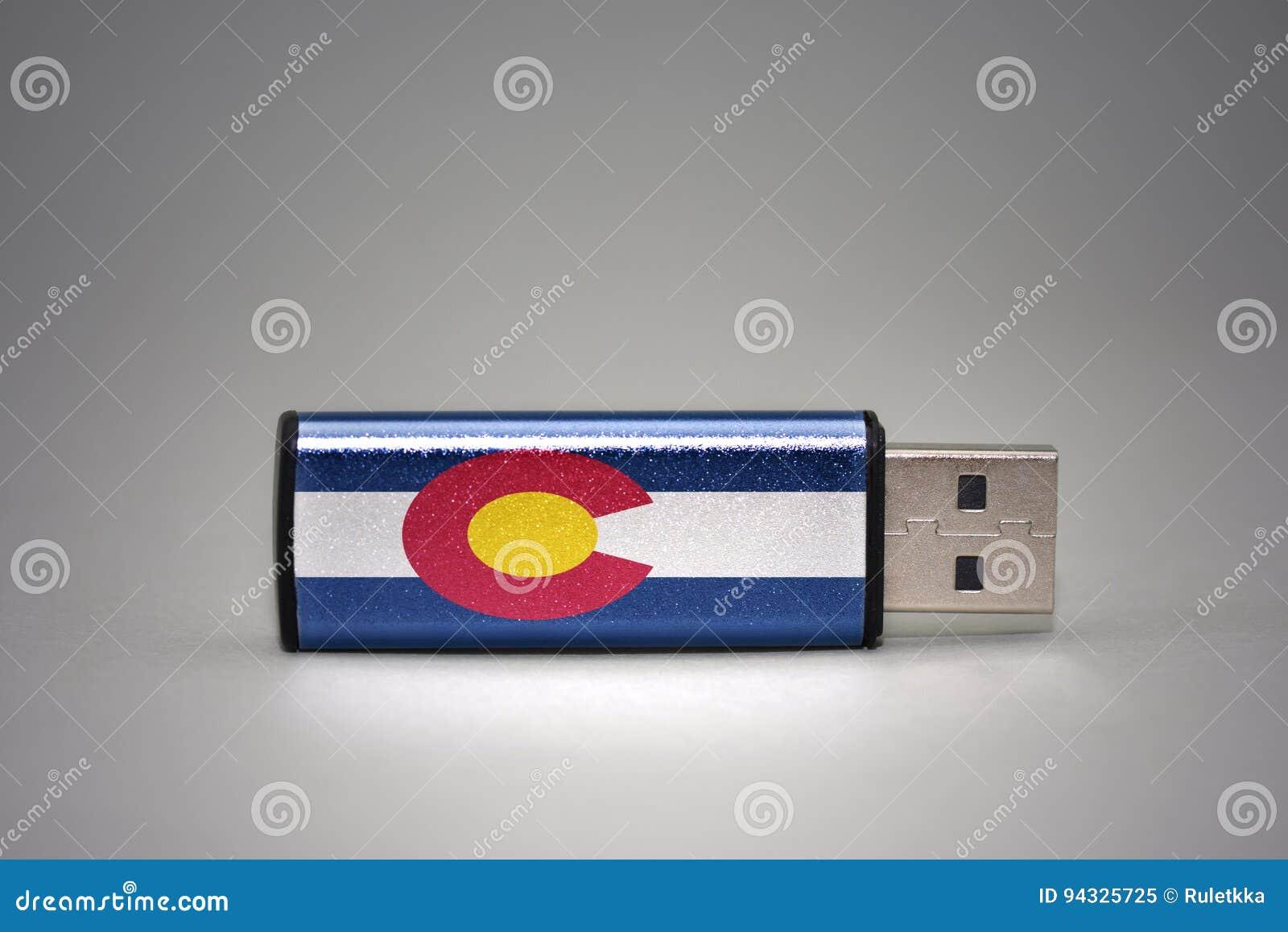 Movimentação do flash do Usb com a bandeira do estado de Colorado no fundo cinzento