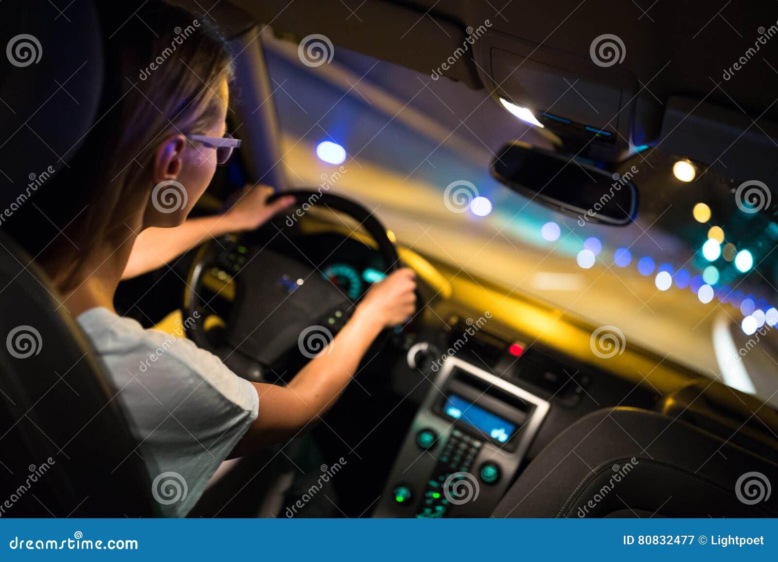 Movimentação fêmea que conduz um carro na noite