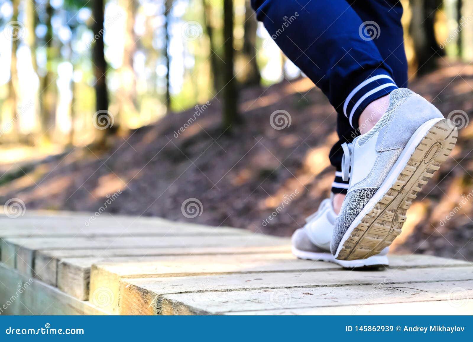 Movimentar-se nas sapatilhas na ponte no parque Esporte, saúde e conceito físico da cultura