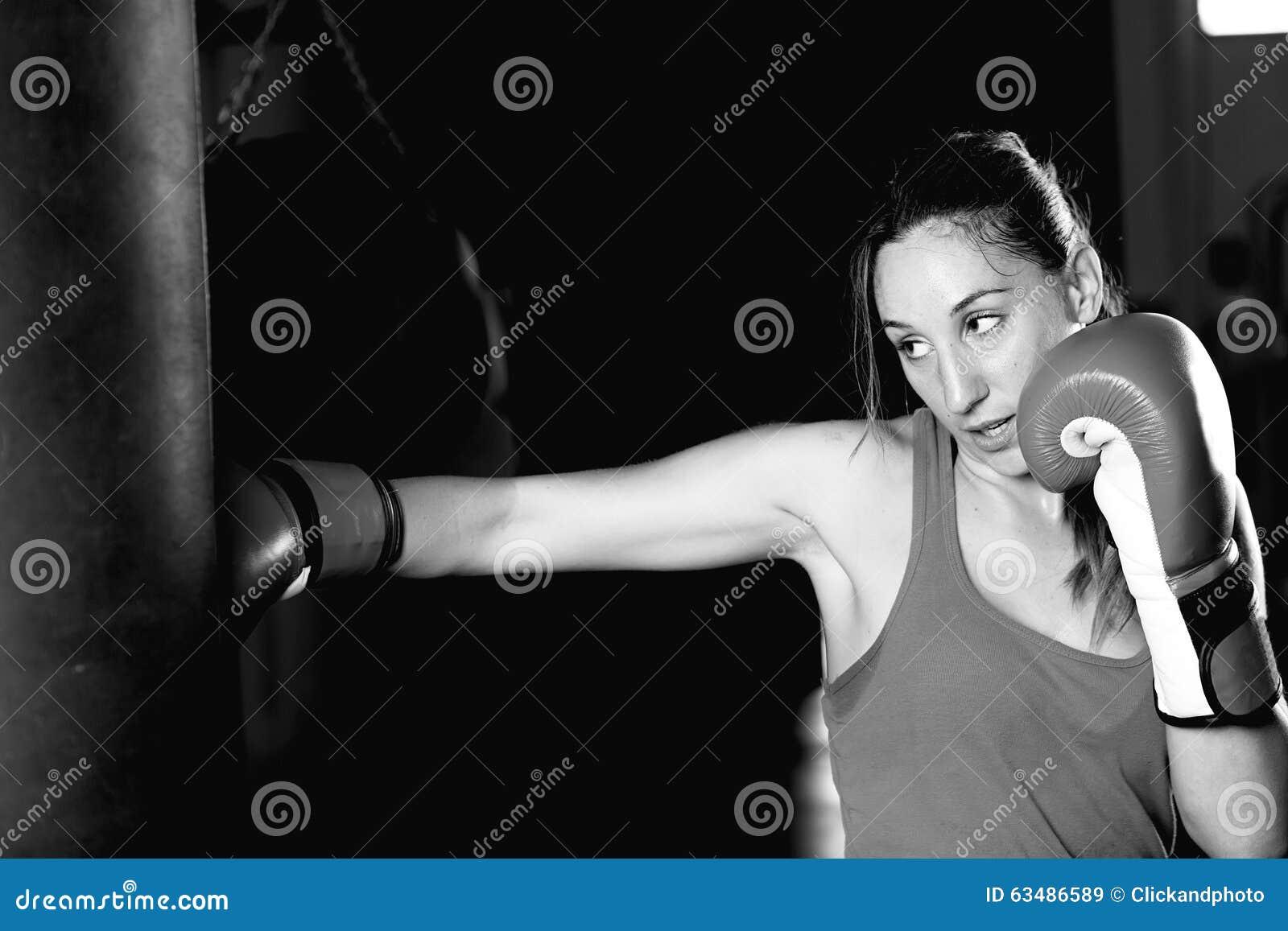 Movimientos practicantes del boxeador de sexo femenino en el saco de arena