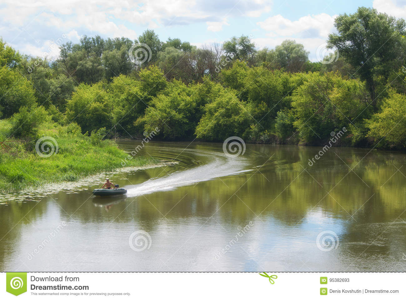 Moving on a motor boat on a river with forested coasts