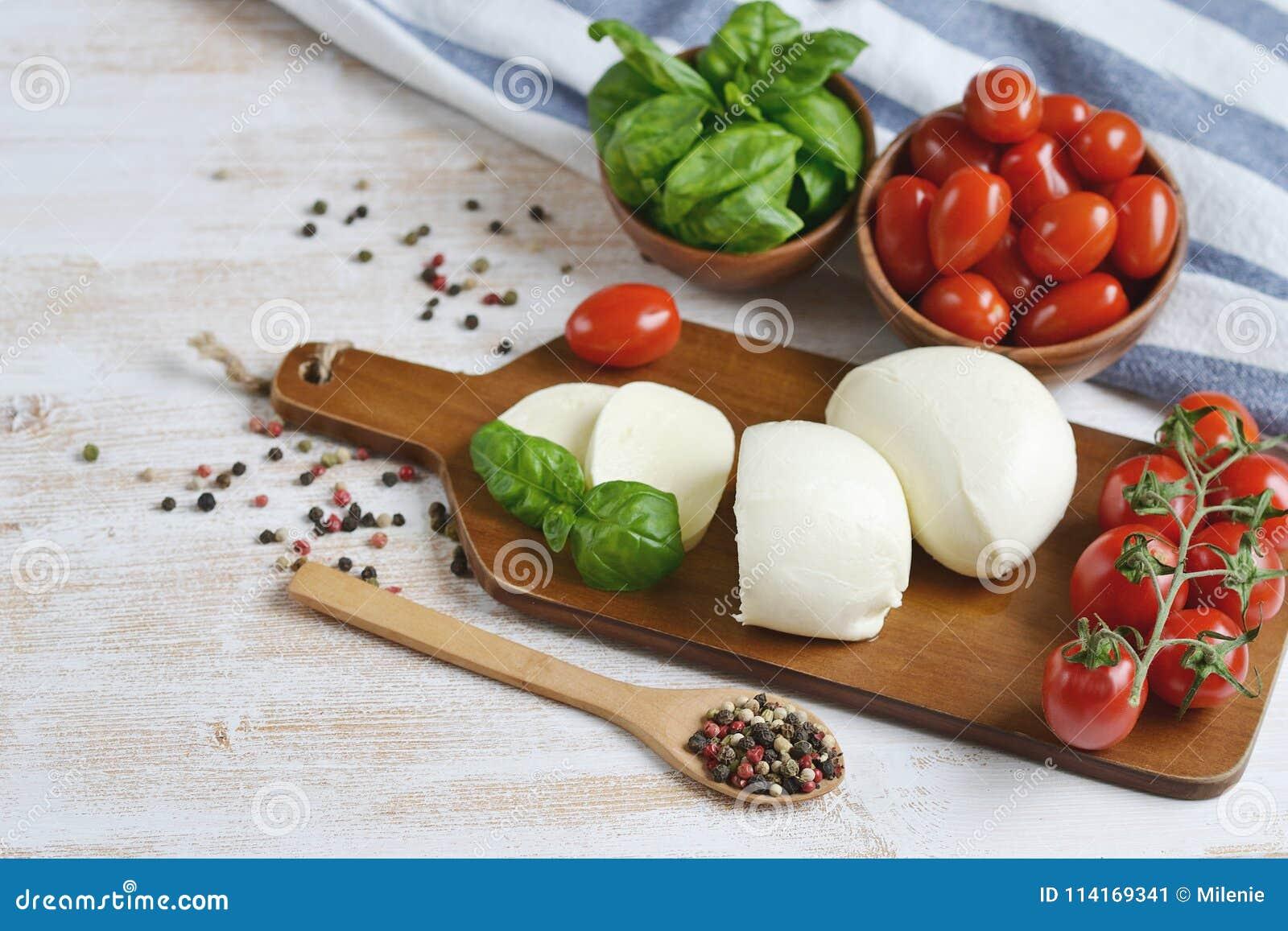 Mozarellakaas met rode tomaten en basilicumbladeren, peper, olijfolie