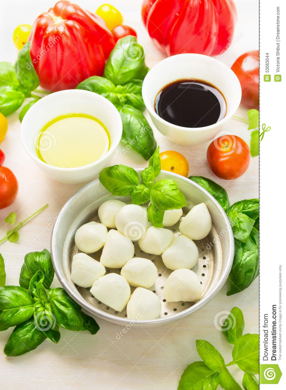 Mozzarella in bowl with basil leaves,oil,tomatoes and balsamic vinegar, italian food ingredients