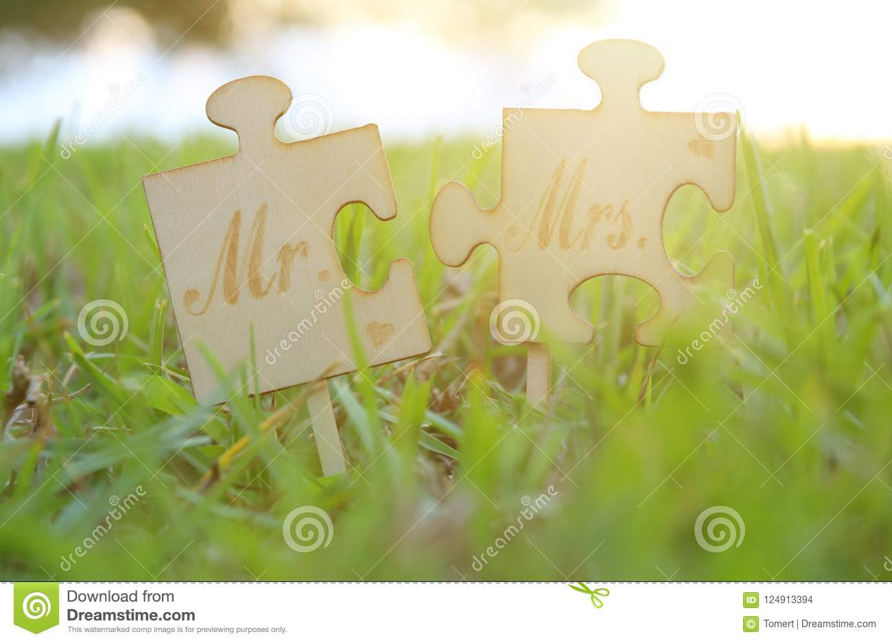Mr and Mrs sign. Two puzzle pieces placed in the grass during sunset time. harmony and wedding concept.