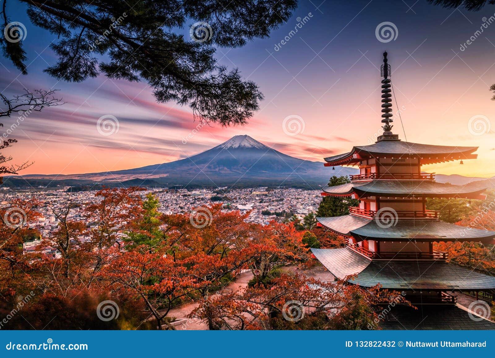 Mt Фудзи с пагодой Chureito и красными лист в осени на солнцах