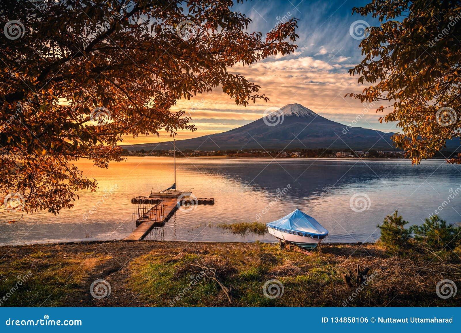 Mt Fuji sobre o lago Kawaguchiko com folha do outono e o barco no nascer do sol em Fujikawaguchiko