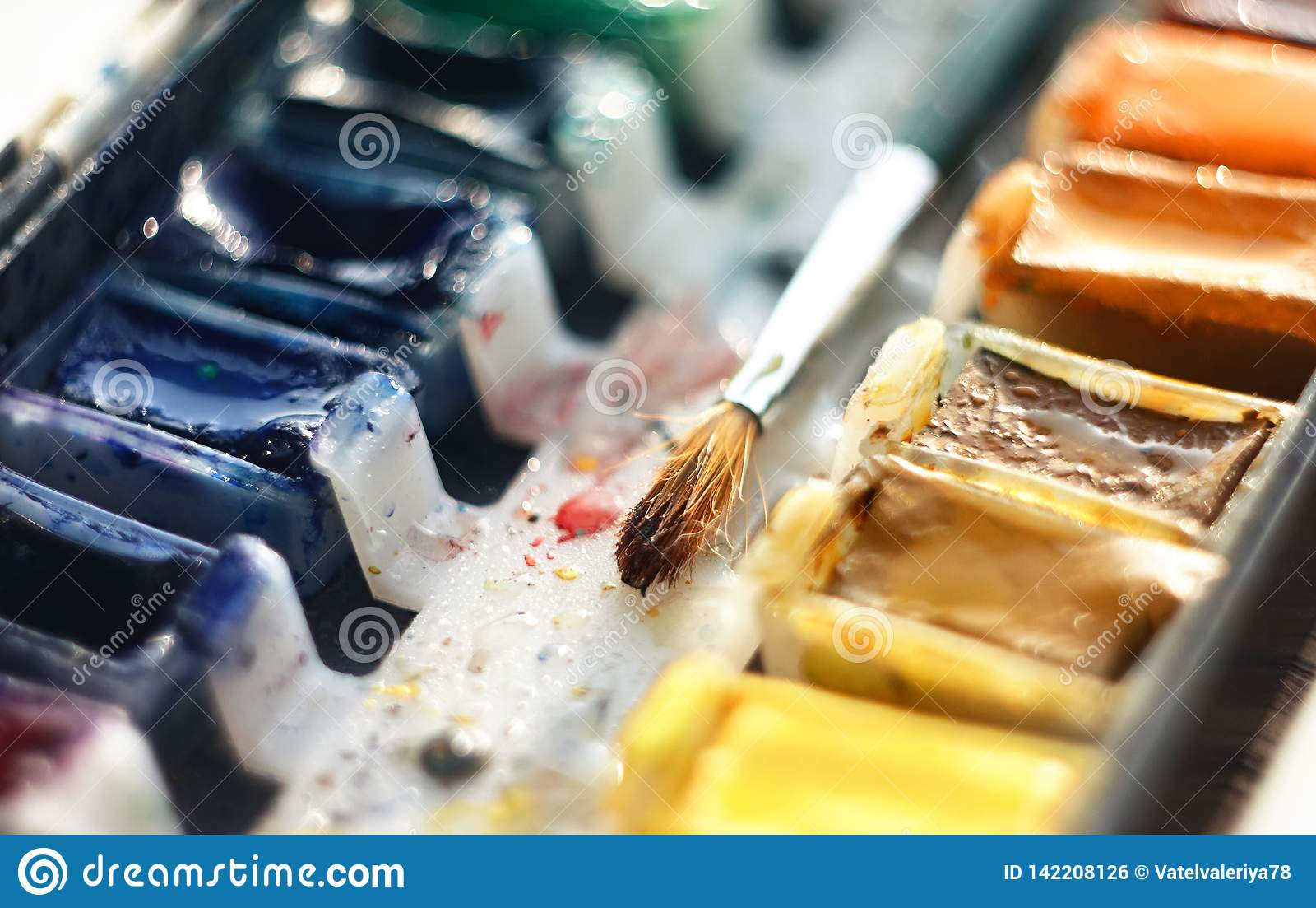 Muśnięcie dla rysować kłama wśród cuvettes z akwareli farbą