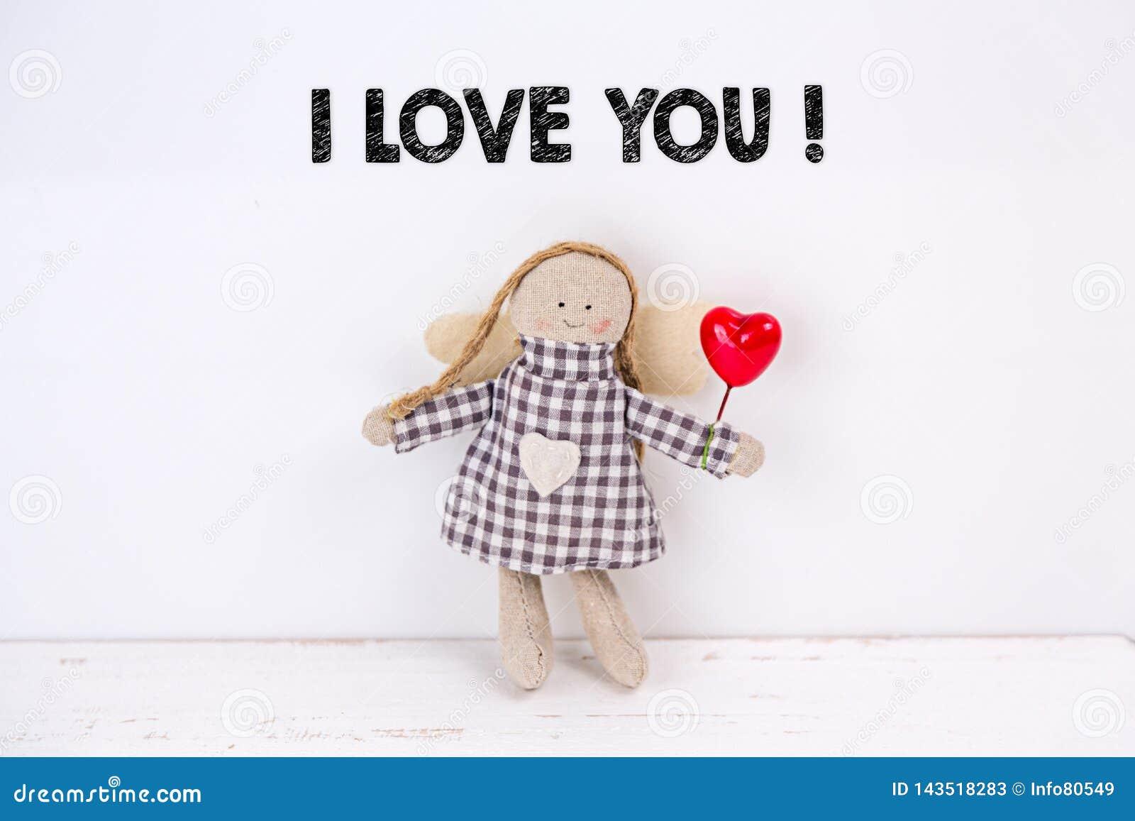Mu?eca de la marioneta con un coraz?n y un texto rojos ?te amo ?en un fondo blanco