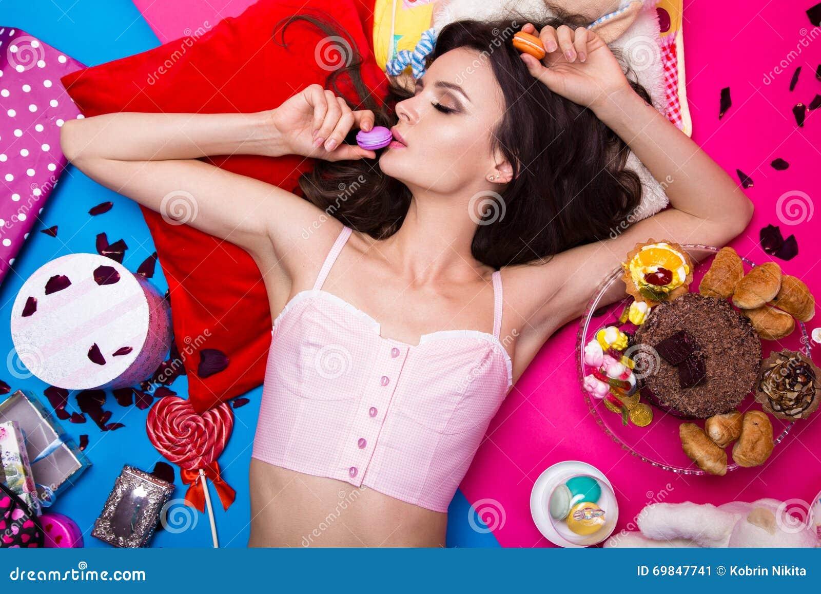 Muñeca fresca hermosa de la muchacha que miente en los fondos brillantes rodeados por los dulces, los cosméticos y los regalos Es