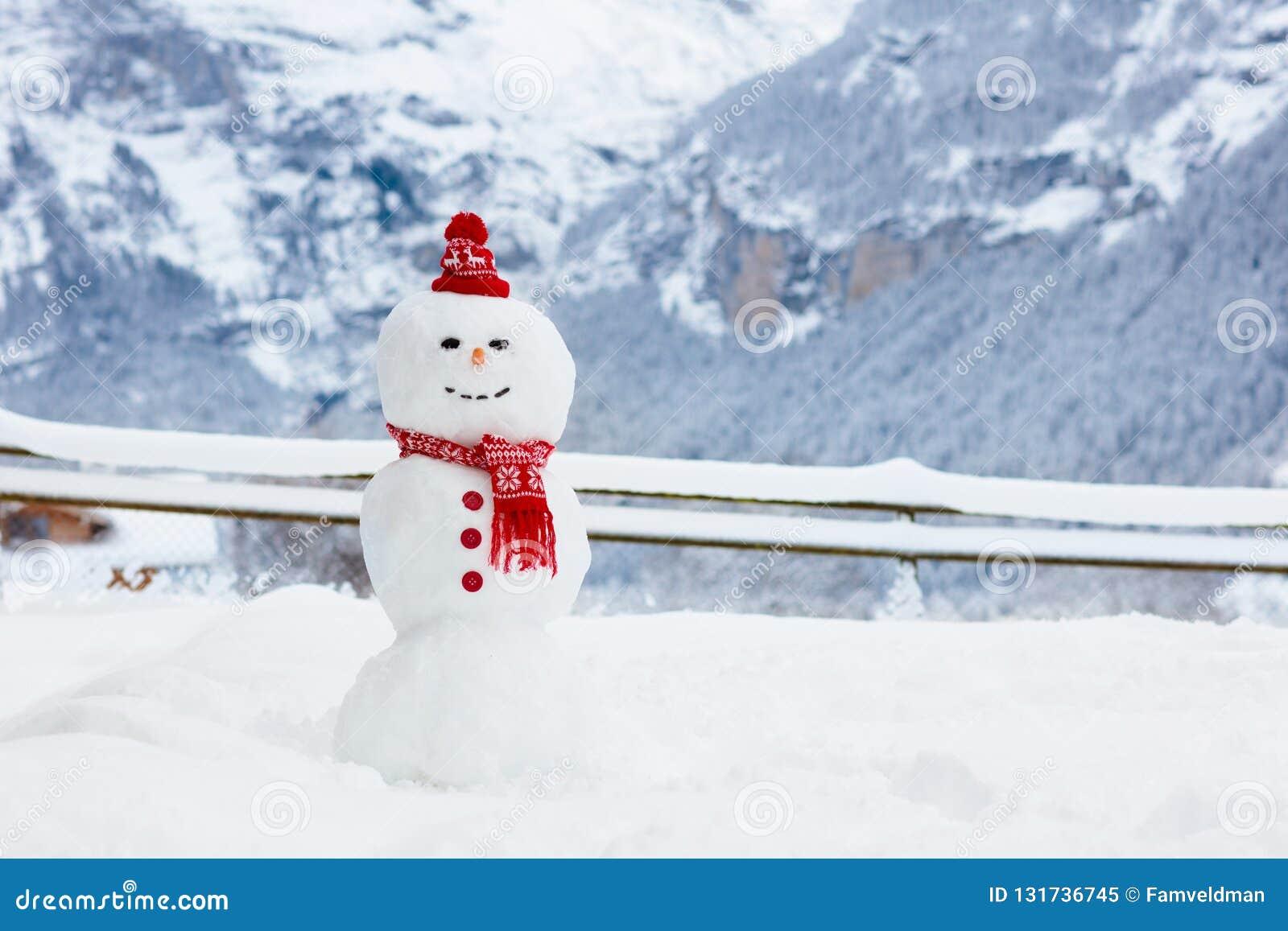 Muñeco de nieve en montañas de las montañas Diversión del edificio del hombre de la nieve en paisaje de la montaña del invierno A