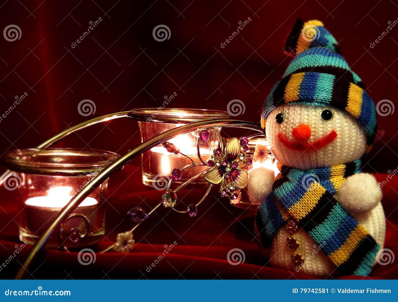 Muñeco de nieve y velas de fondo rojo oscuro de la tela