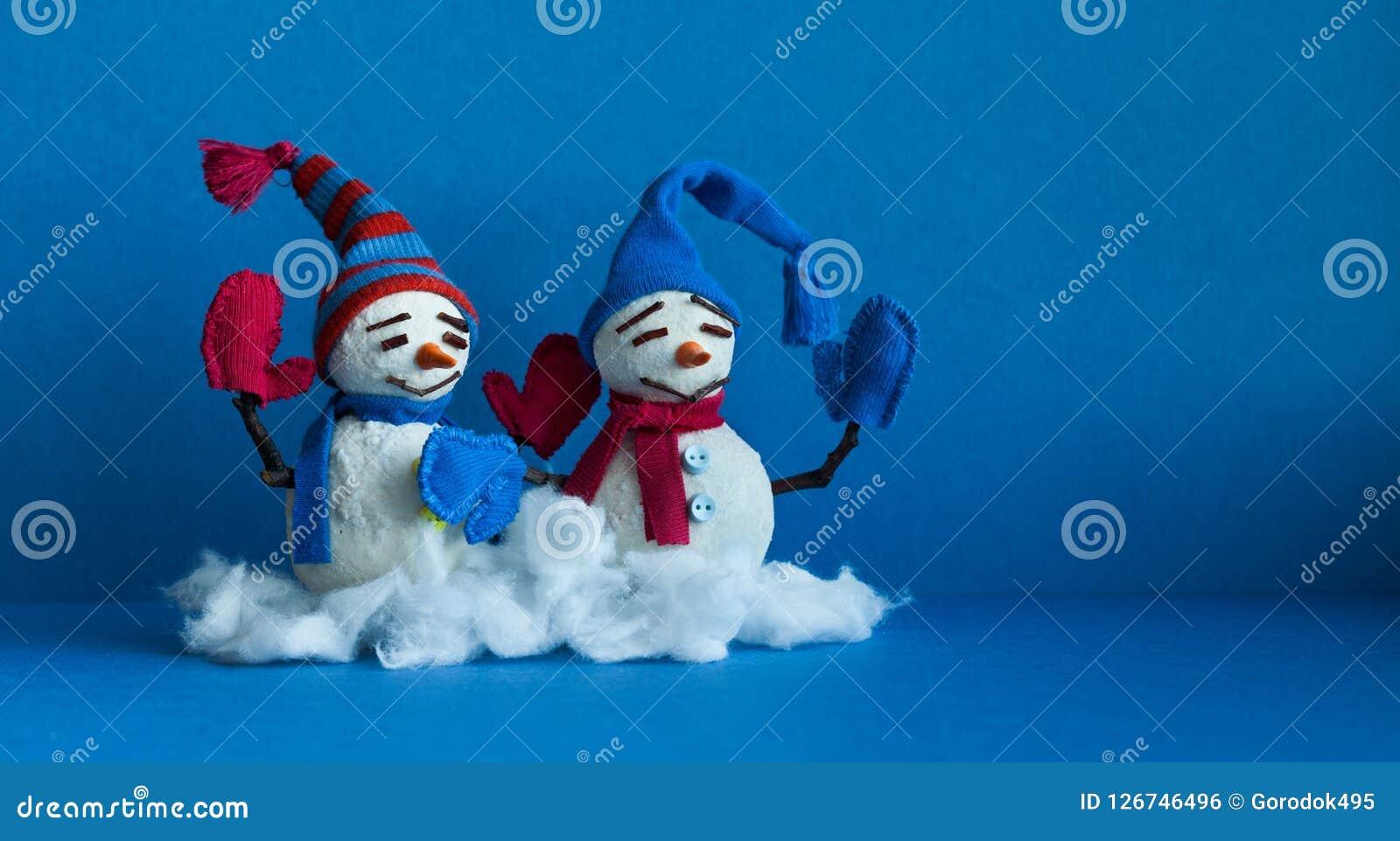 Muñecos de nieve felices en fondo azul Caracteres tradicionales del muñeco de nieve del invierno con las manoplas de la bufanda y