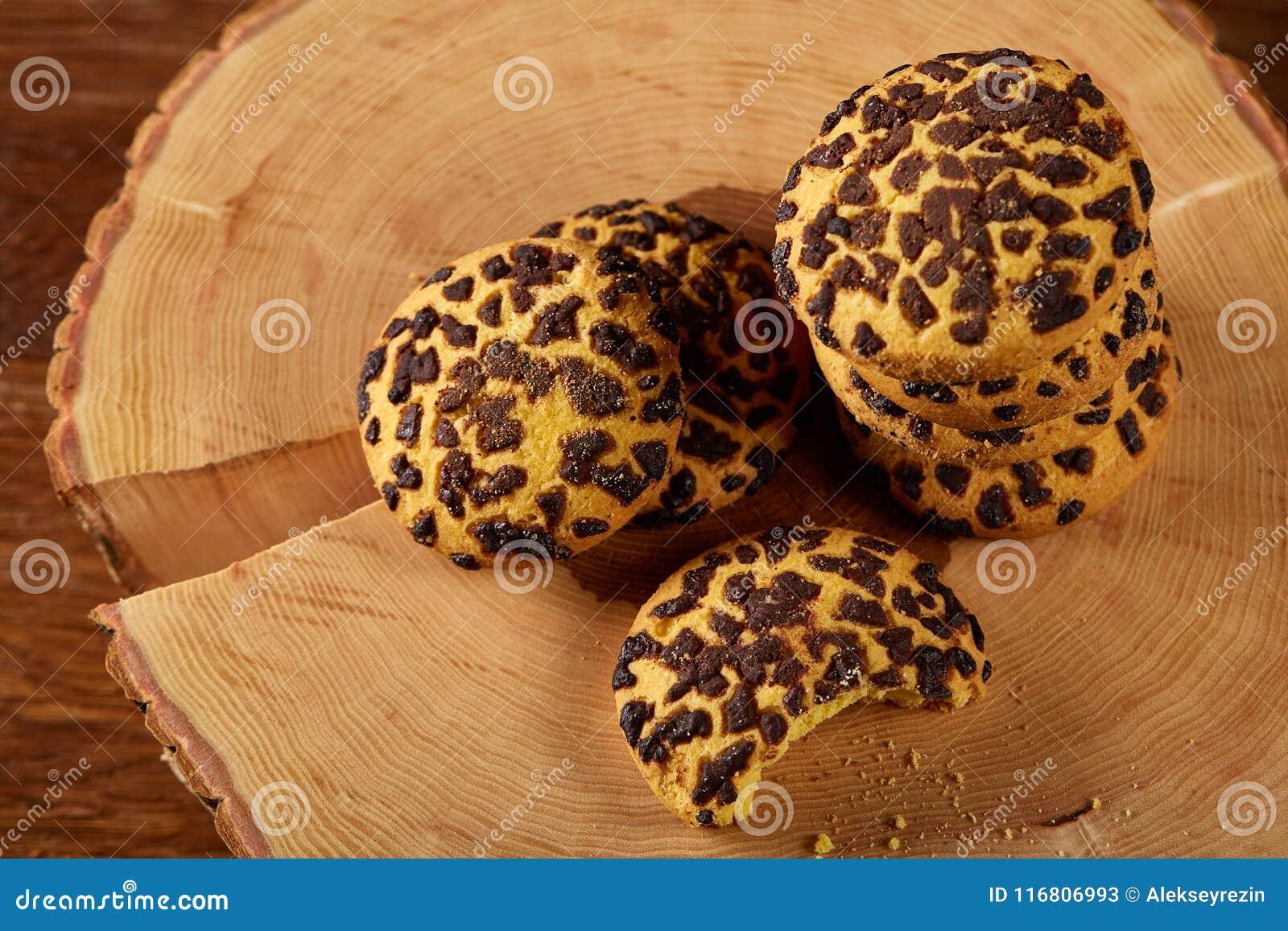 Mucchio dei biscotti su un ceppo di legno rotondo sopra fondo di legno rustico, primo piano, fuoco selettivo