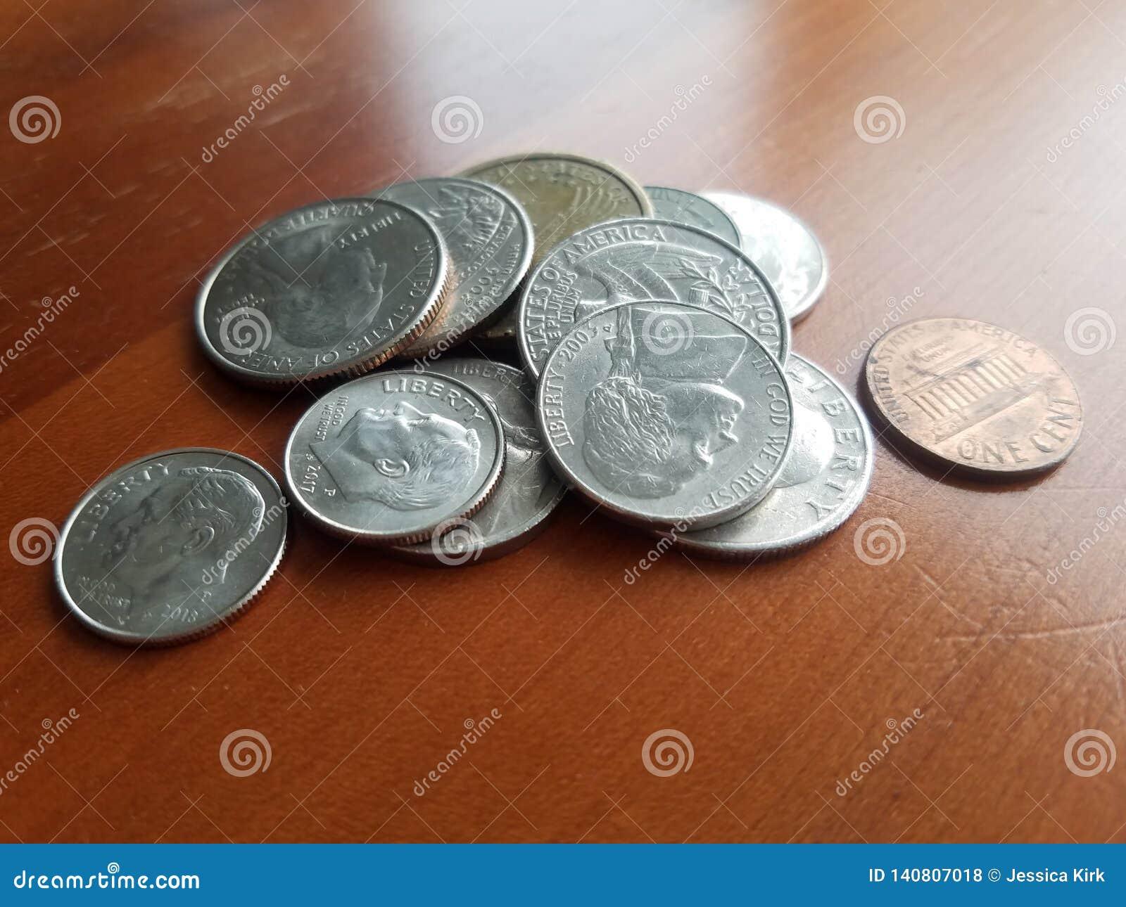 Mucchio del quarto di libertà di valuta degli Stati Uniti e di altre monete sulla tavola di legno