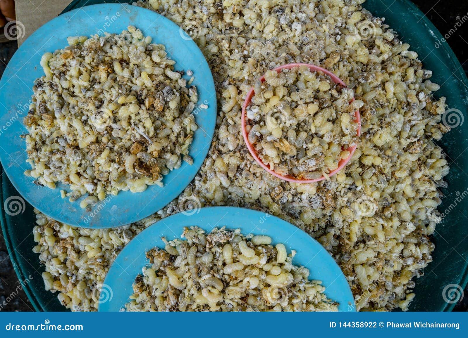 Mucchio delle uova rosse della formica vendute in un mercato locale in Tailandia del Nord