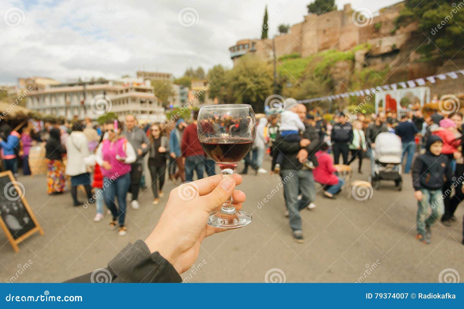 Mucha gente con las familias que caminan las calles de la celebración con el vino durante el festival Tbilisoba País de Tbilisi,