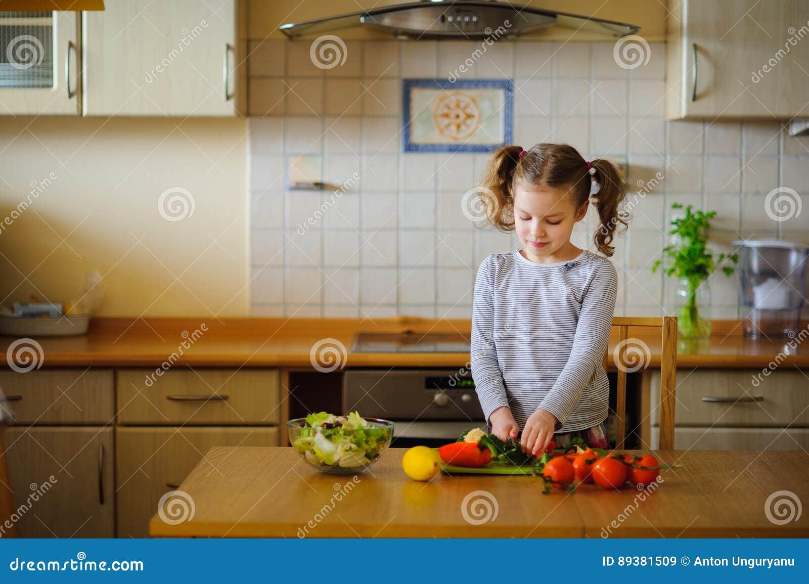 Muchacha 8-9 años en la cocina que corta las verduras para una ensalada