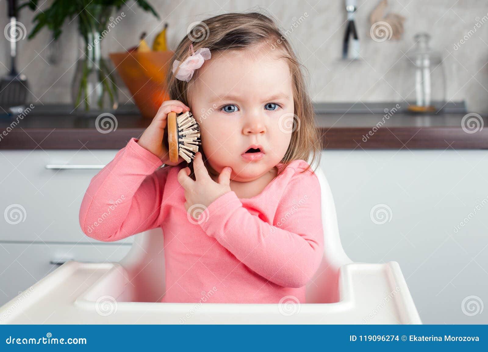 Muchacha 2 años que juegan con retratar del peine en casa - una conversación emocional sobre el teléfono