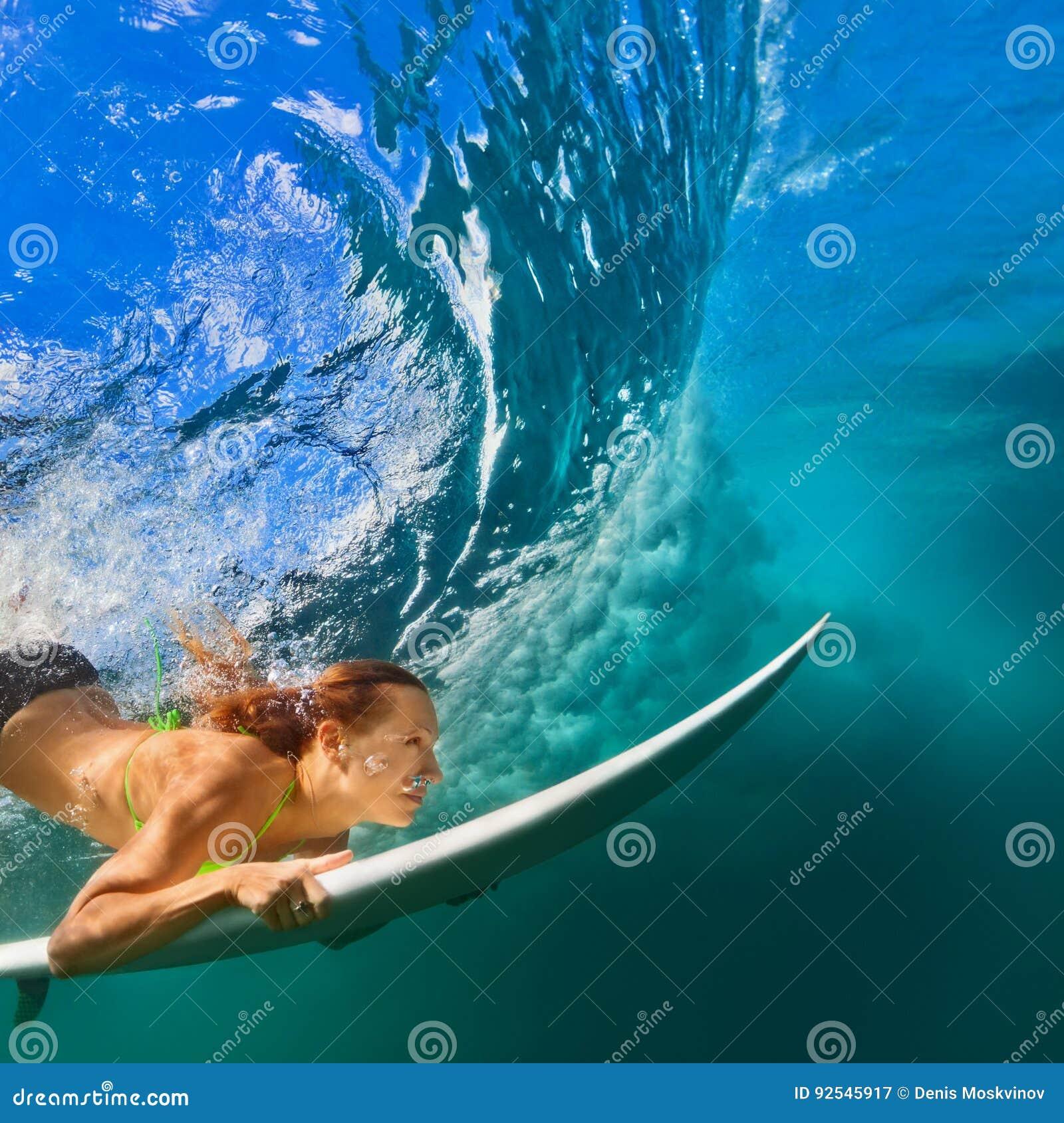Muchacha activa en bikini en la acción de la zambullida en el tablero de resaca