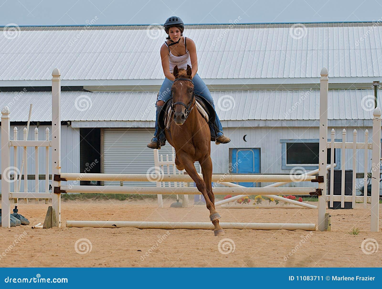 Muchacha adolescente atlética que salta un caballo sobre los carriles.