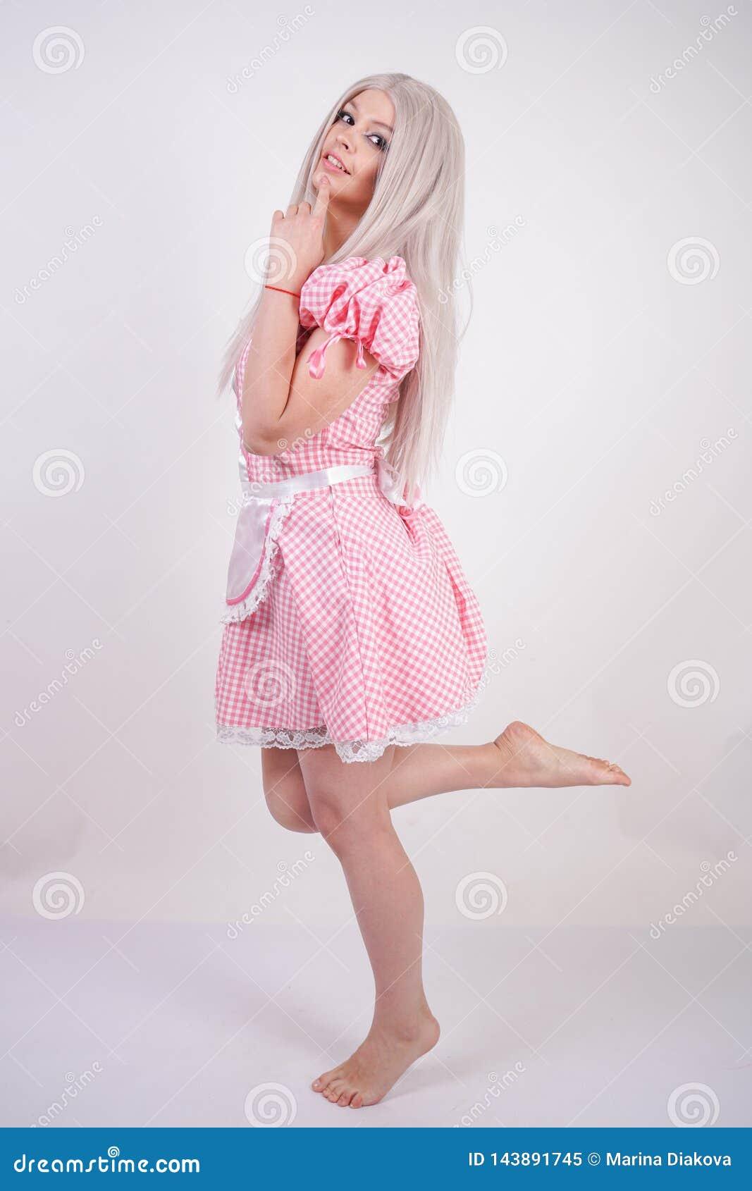 Muchacha adolescente caucásica joven linda en vestido bávaro de la tela escocesa del rosa con el delantal que presenta en fondo s
