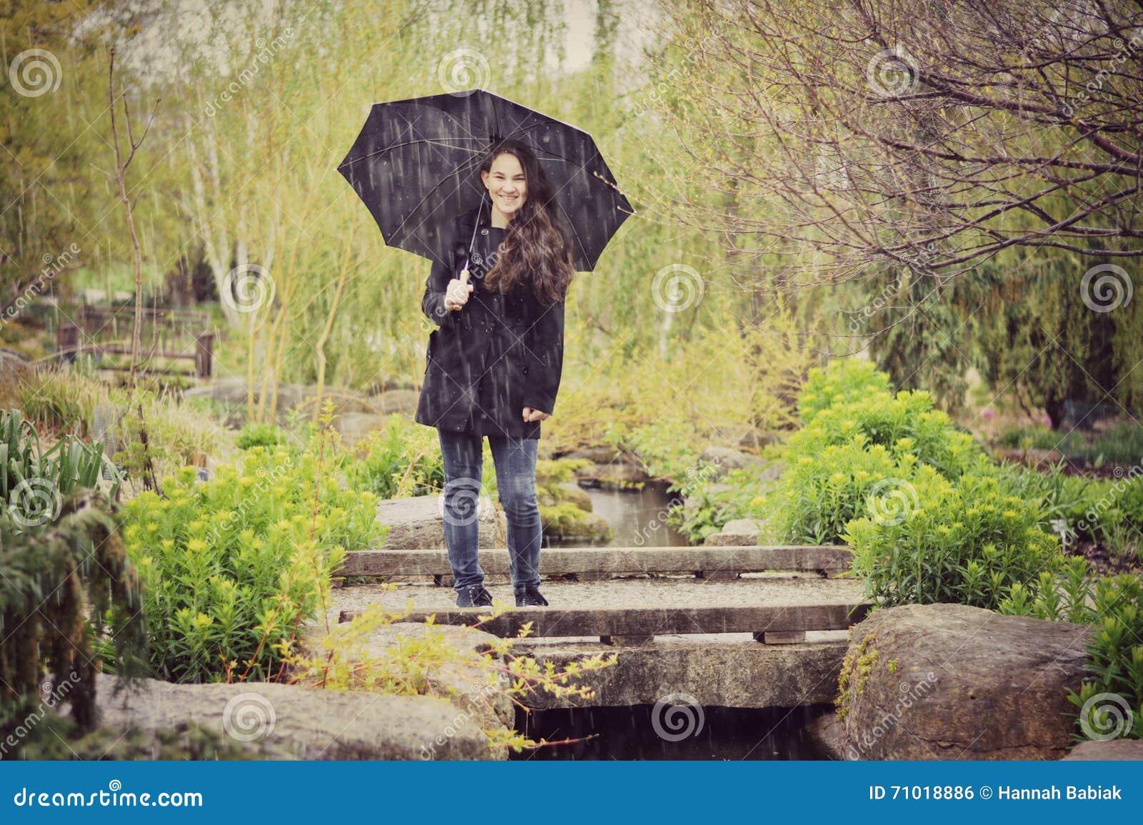 Muchacha adolescente con el paraguas en lluvia
