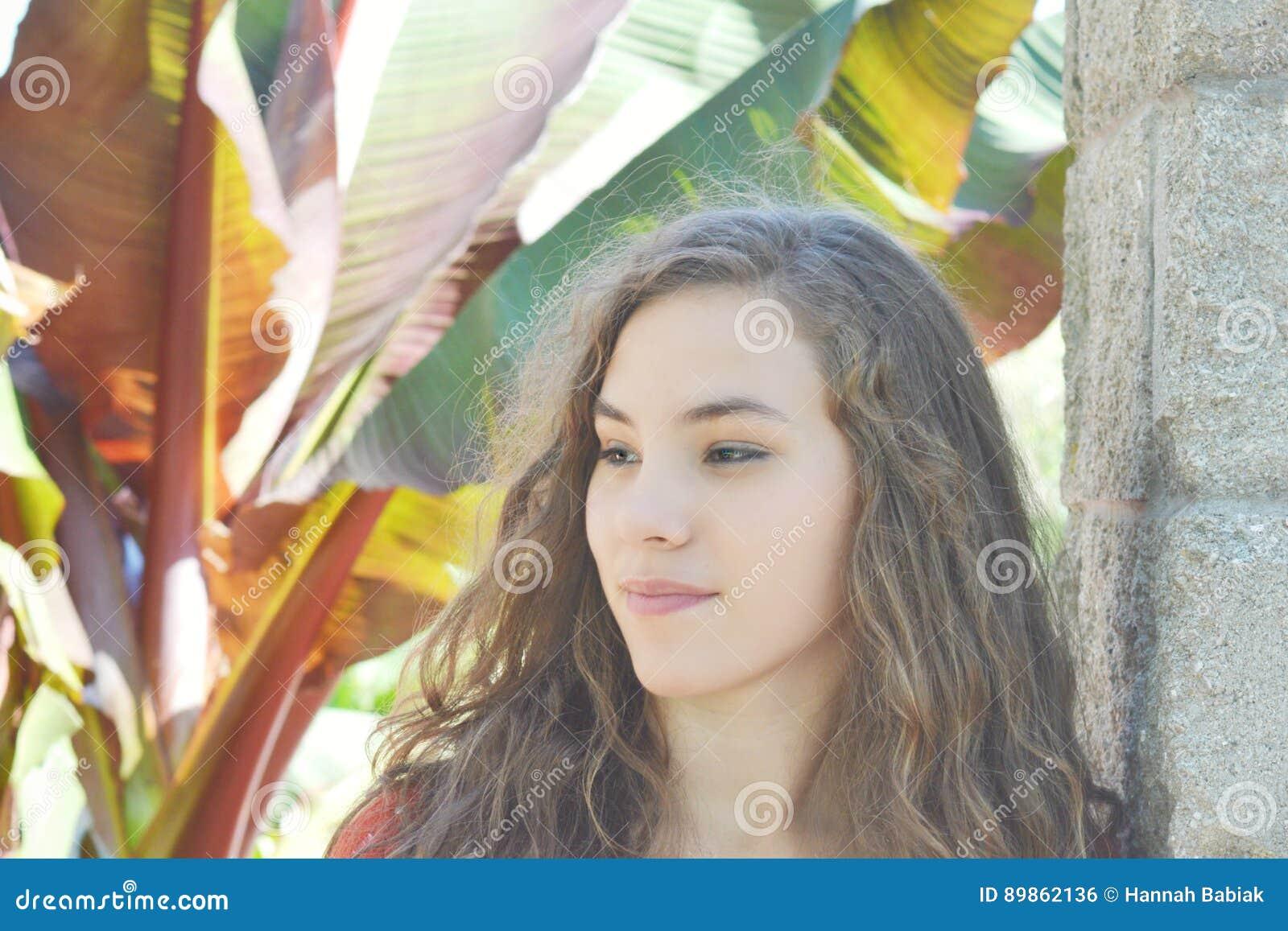 Muchacha adolescente con las plantas tropicales