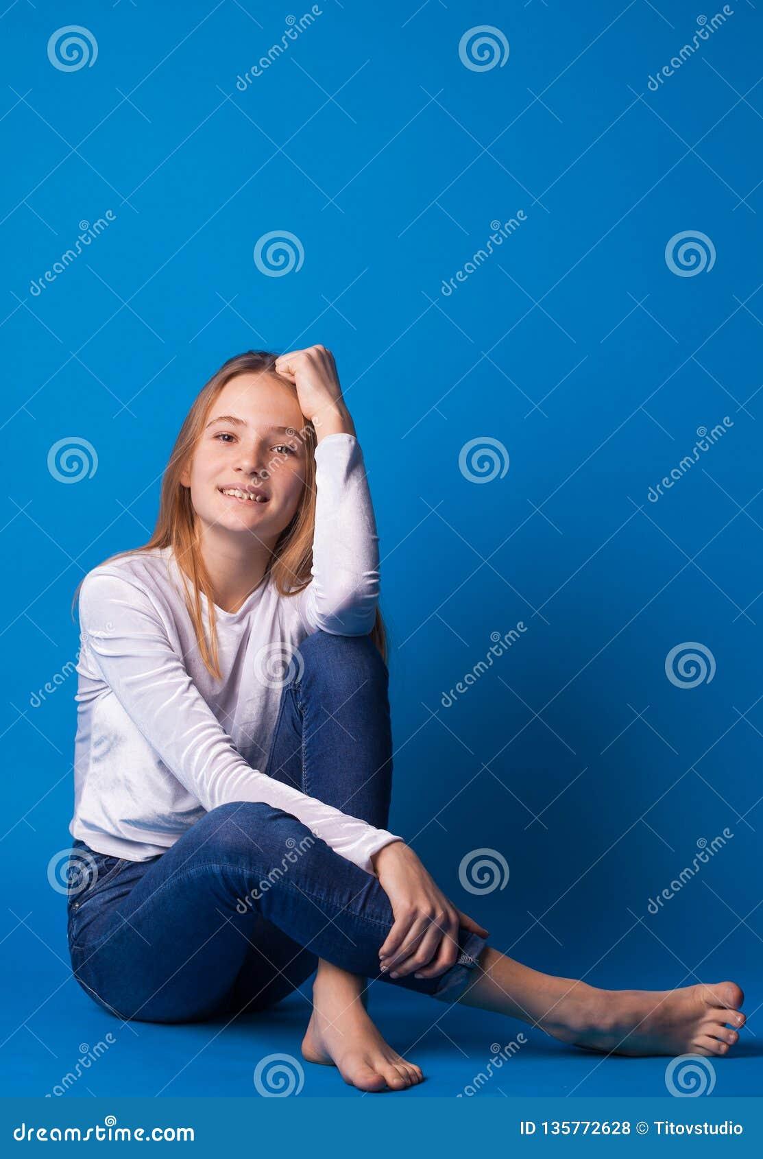 Muchacha adolescente elegante hermosa en fondo azul