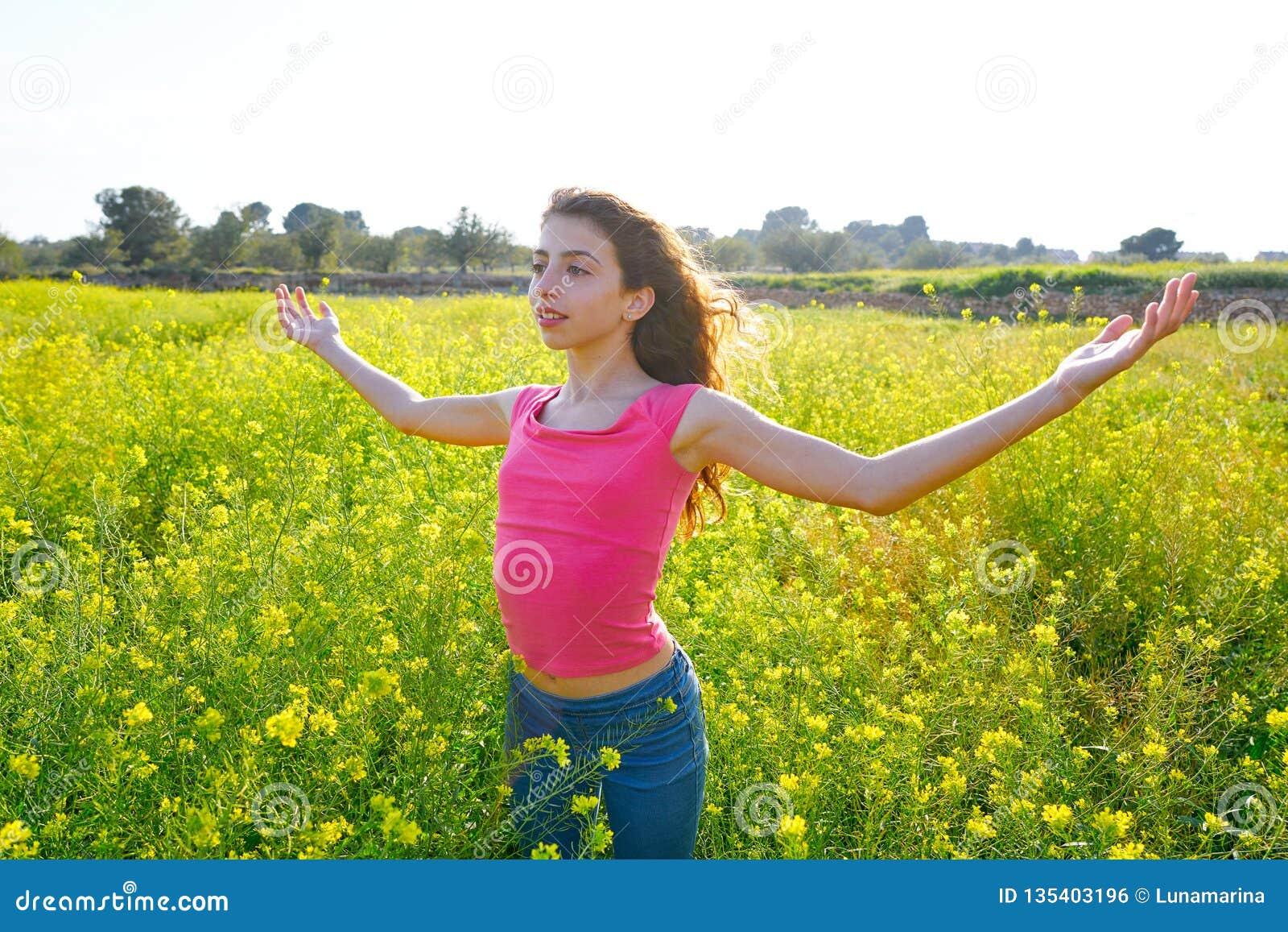 Muchacha adolescente feliz de los brazos abiertos en prado de la primavera