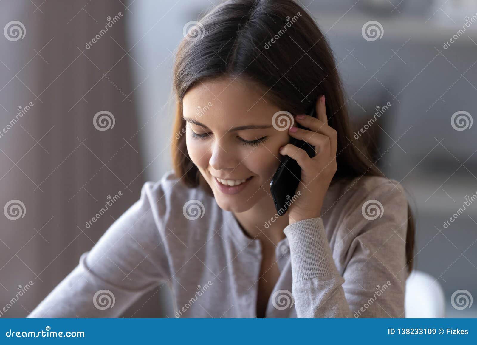 Muchacha adolescente feliz que habla en el teléfono que tiene conversación móvil agradable