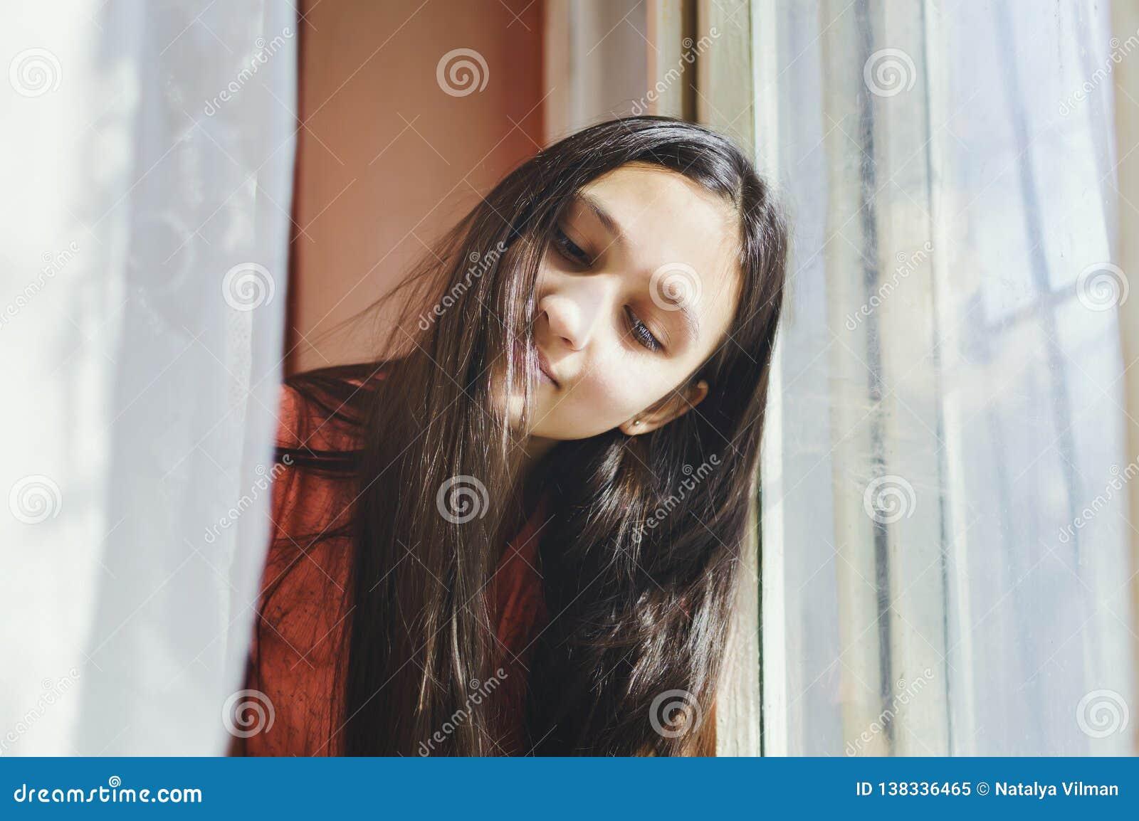 Muchacha adolescente hermosa que se sienta por la ventana