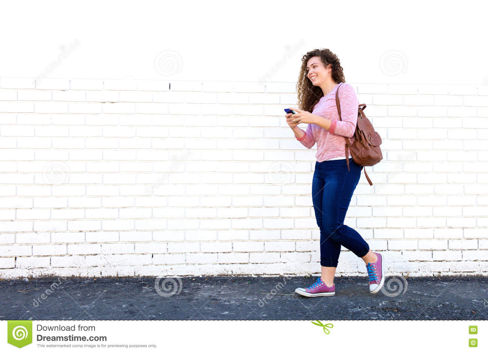 Muchacha adolescente sonriente que camina con el teléfono móvil y la mochila