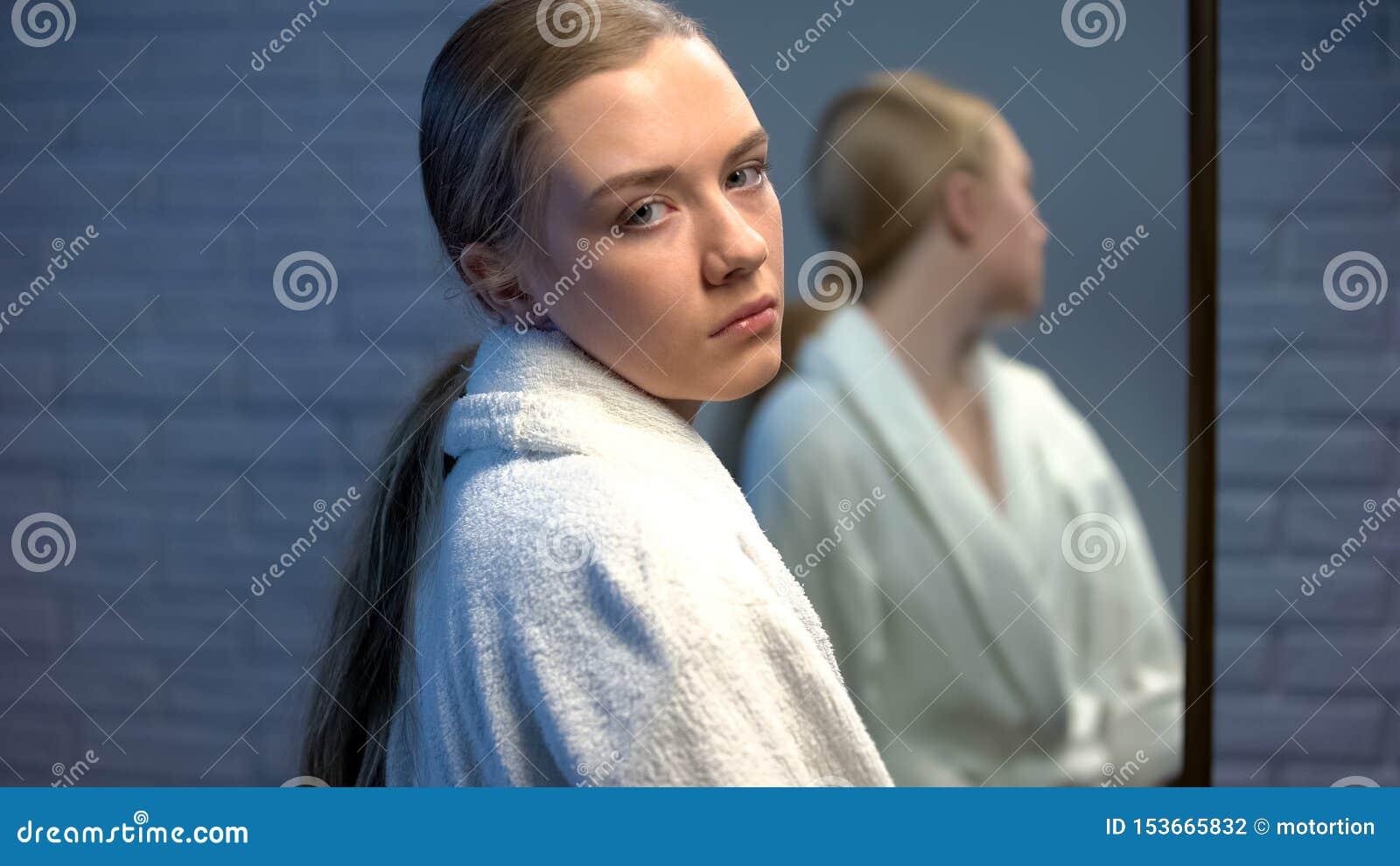Muchacha adolescente trastornada que mira tristemente a la cámara, colocándose delante del espejo, ayuda de la necesidad