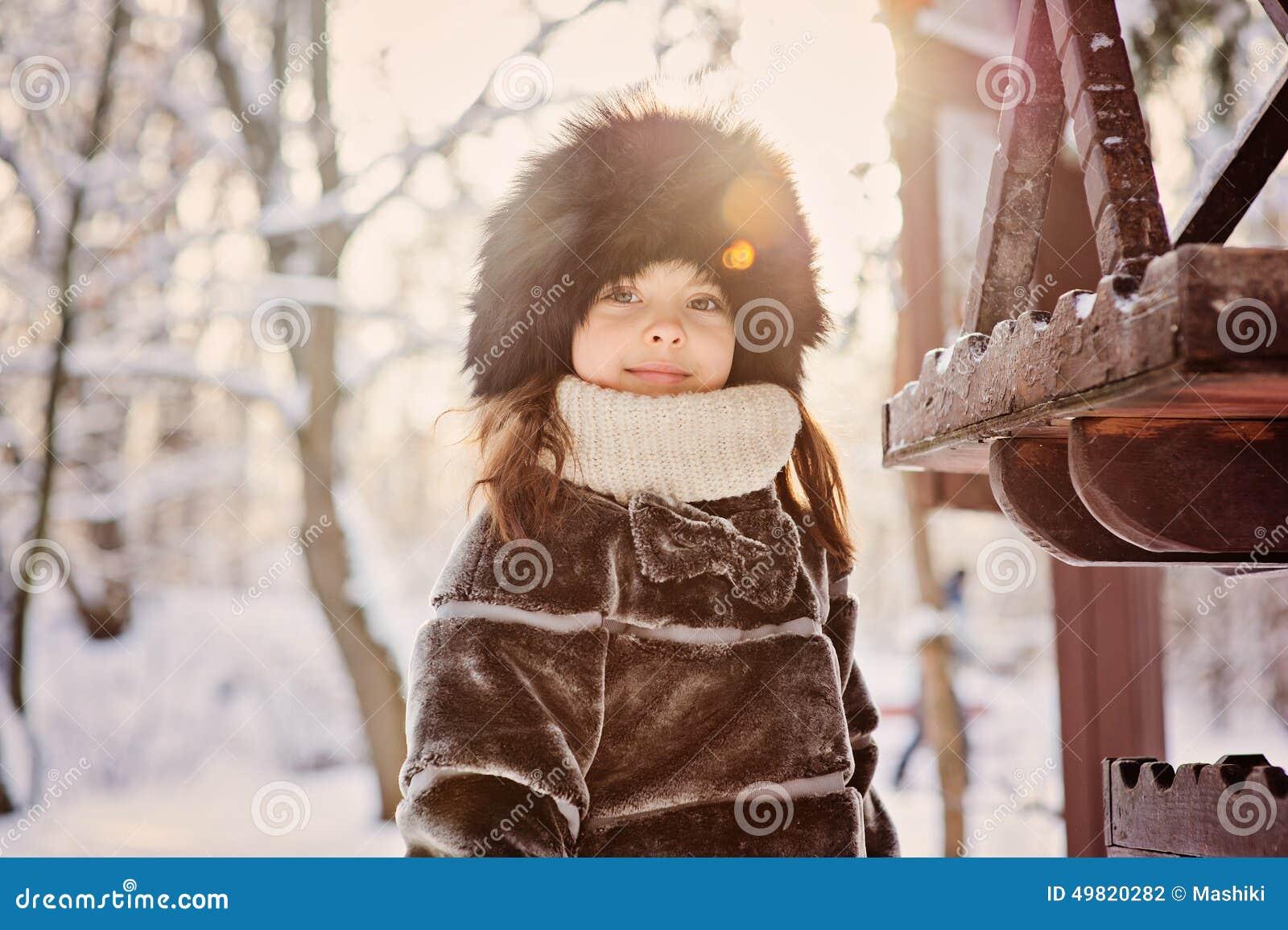 Muchacha adorable feliz del niño en sombrero y capa de piel cerca del alimentador del pájaro en el paseo en bosque del invierno