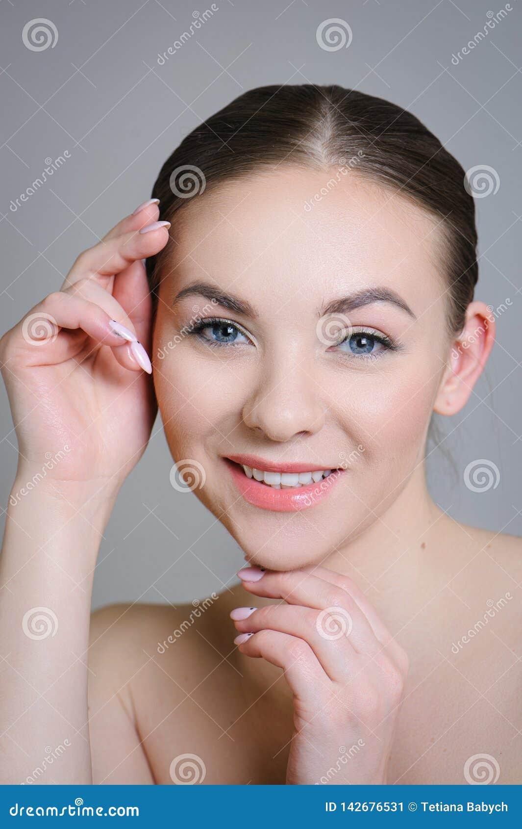 Muchacha adulta hermosa que presenta con maquillaje desnudo con la piel limpia y cuidar su piel