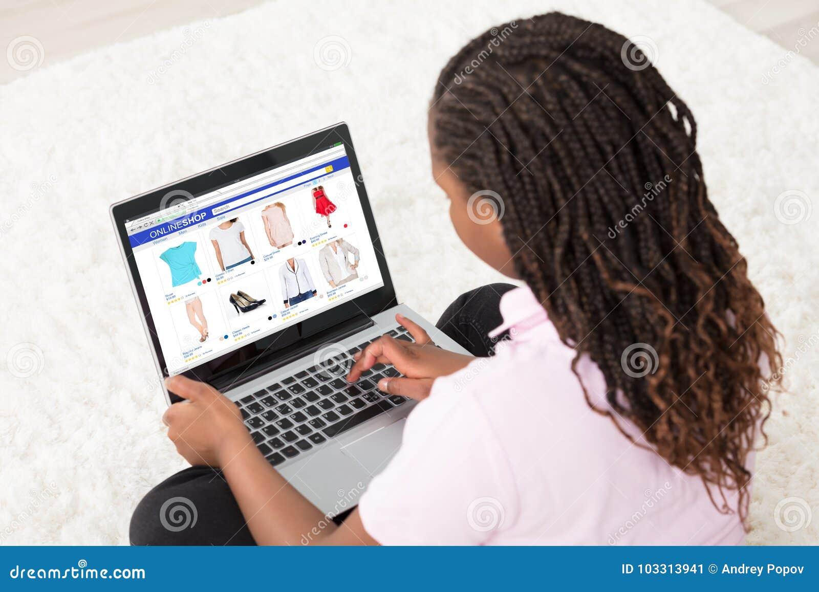 Muchacha africana que hace compras en línea
