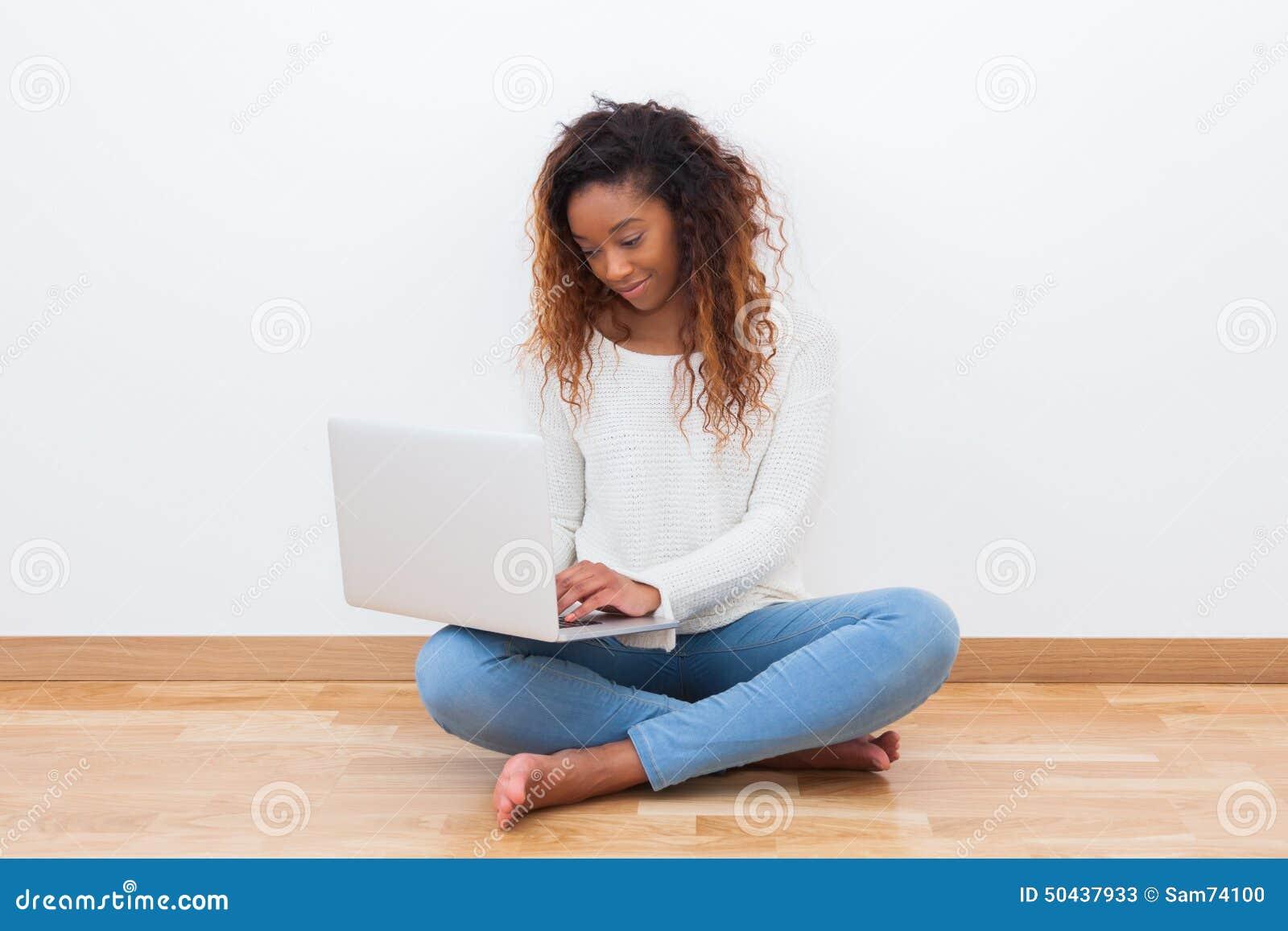 Muchacha afroamericana del estudiante que usa un ordenador portátil - el PE negro