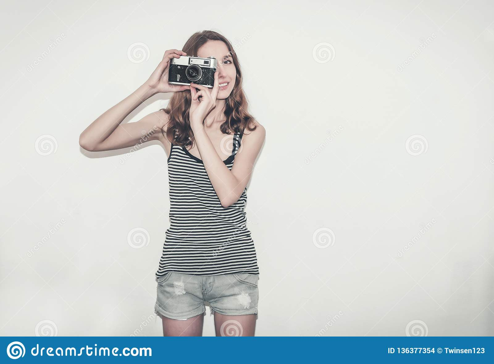 Muchacha agradable en una camiseta rayada con una cámara del vintage en sus manos Fotografía de gente
