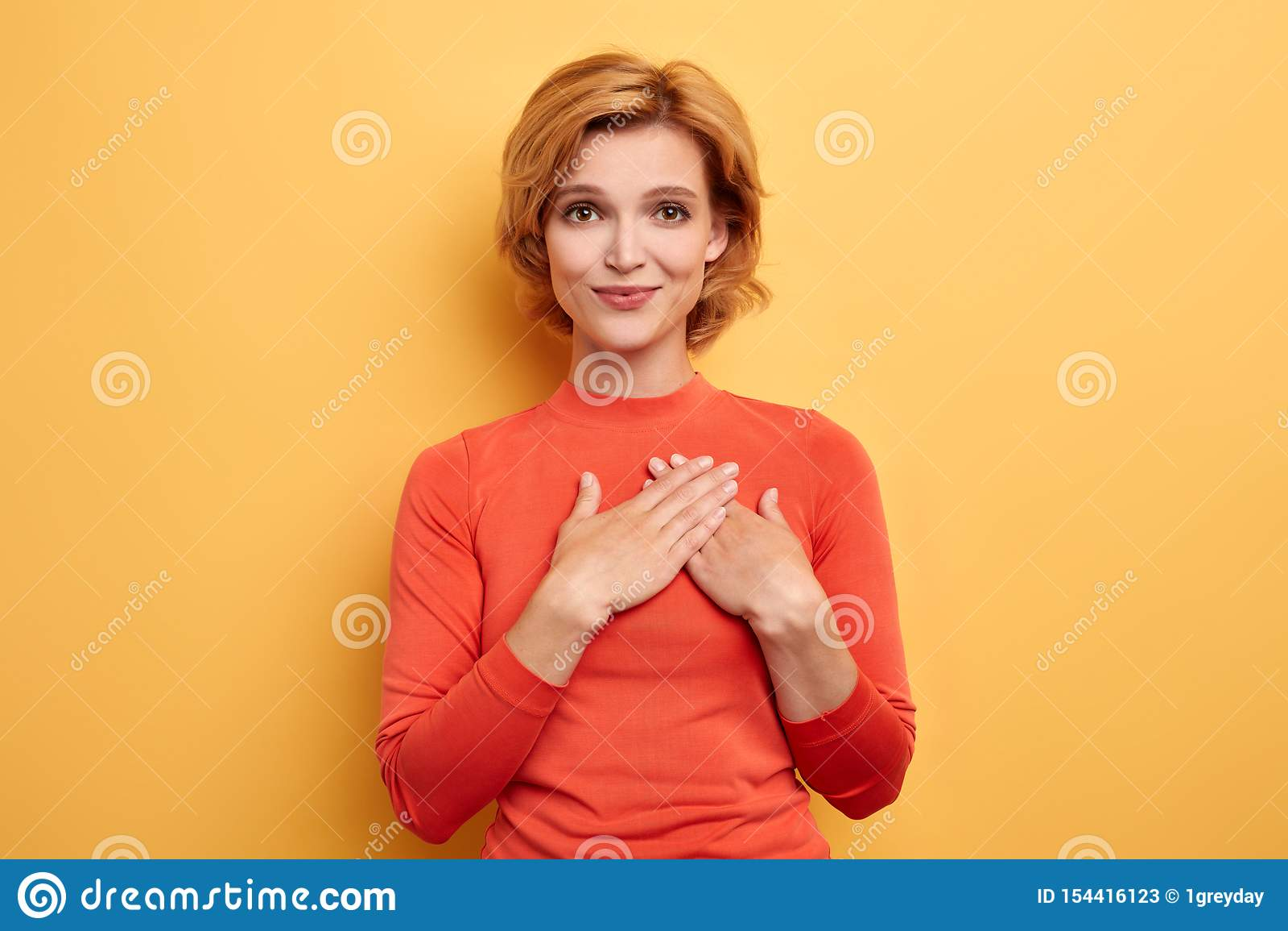 Muchacha agradable sonriente que pone sus palmas en corazón y la mirada de la cámara