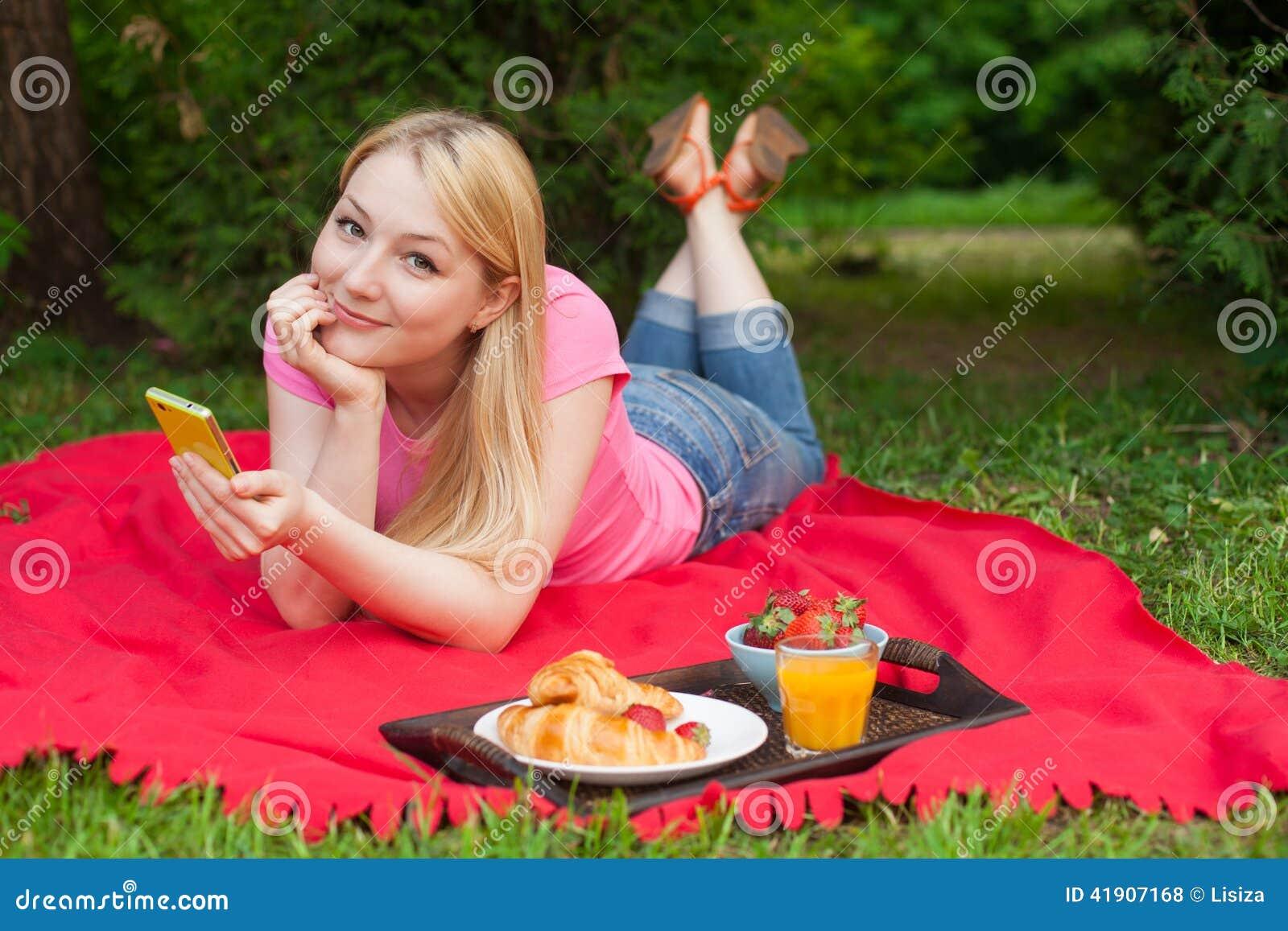 Muchacha al aire libre en el parque en comida campestre usando su teléfono celular