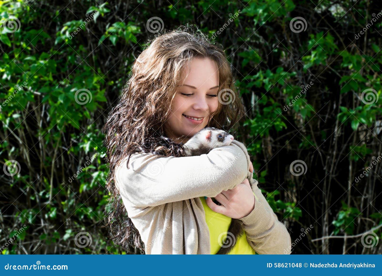Muchacha alegre con el hurón en las manos