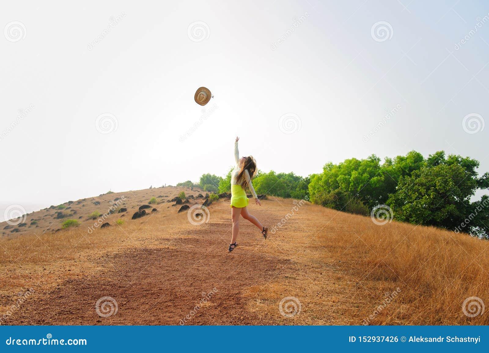 Muchacha alegre con el sombrero de paja largo de los saltos y de los tiros del pelo en el aire Mujer morena joven en paseos de la