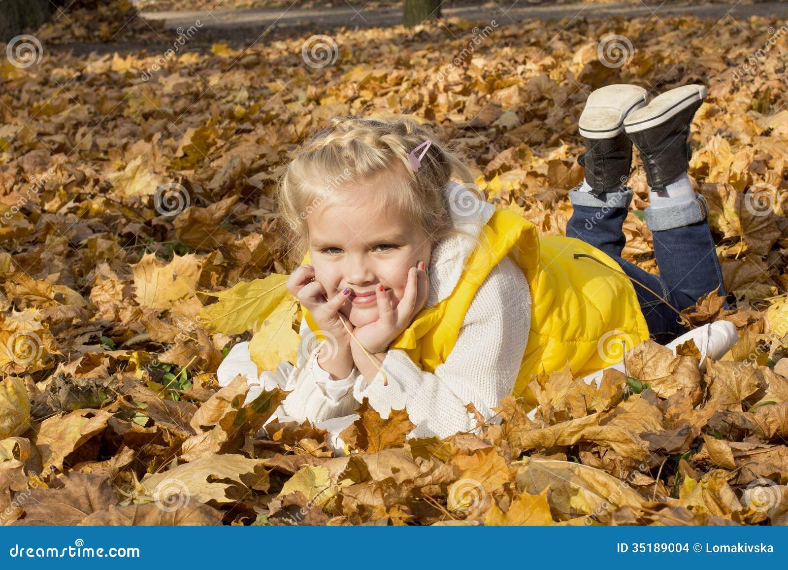 Muchacha alegre hermosa entre las hojas de otoño