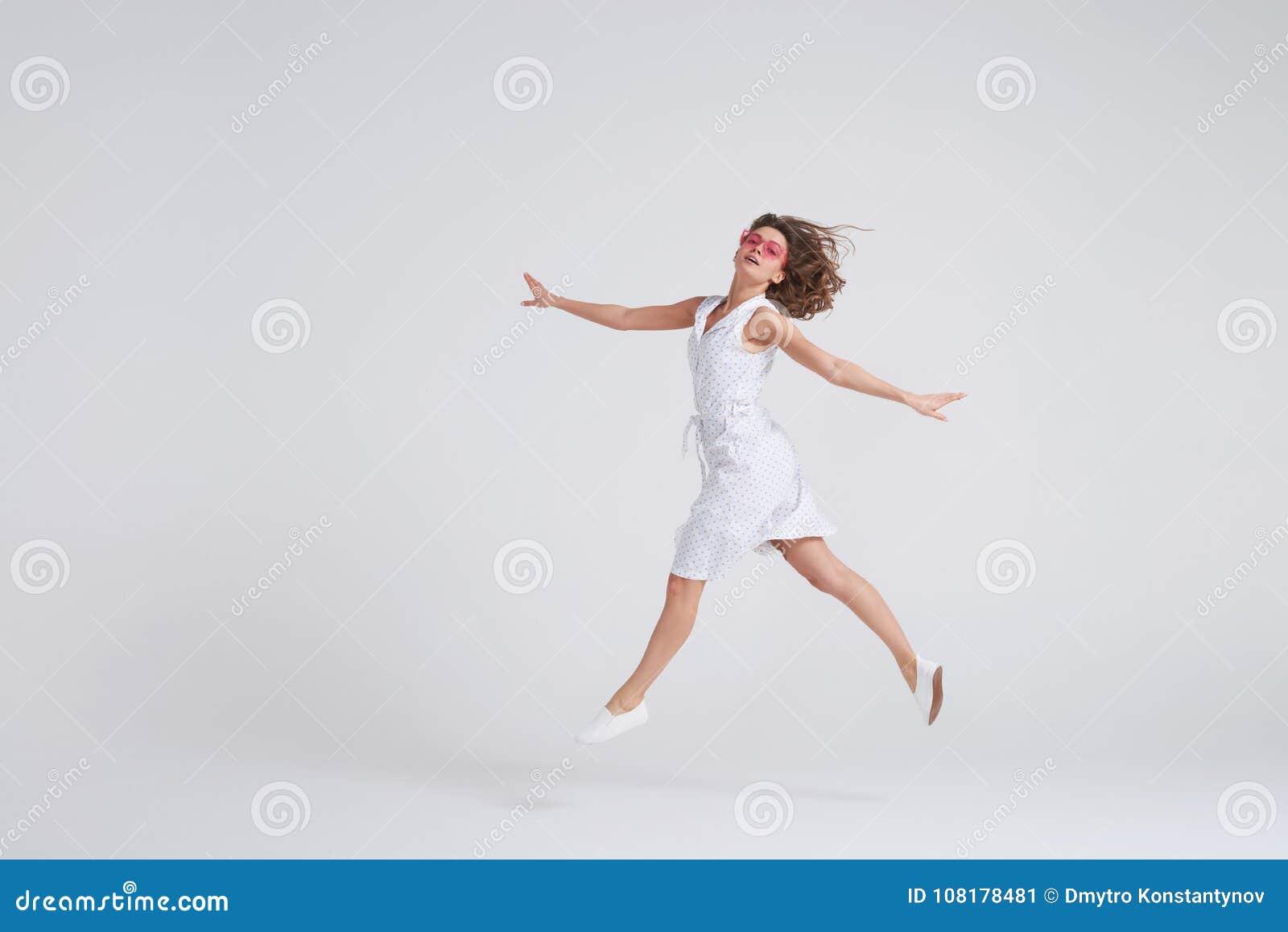 Muchacha alegre que salta en aire sobre el fondo blanco