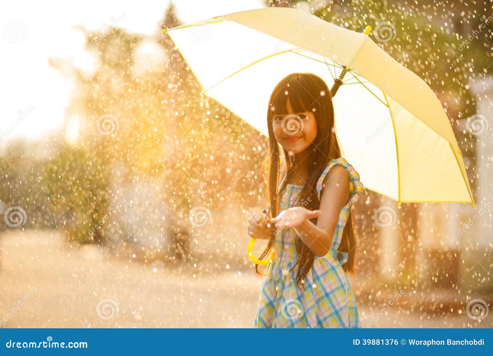 Muchacha asiática bastante joven en la lluvia
