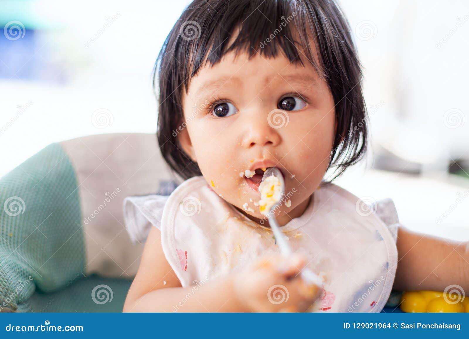Muchacha asiática del niño del bebé lindo que come la comida sana sola